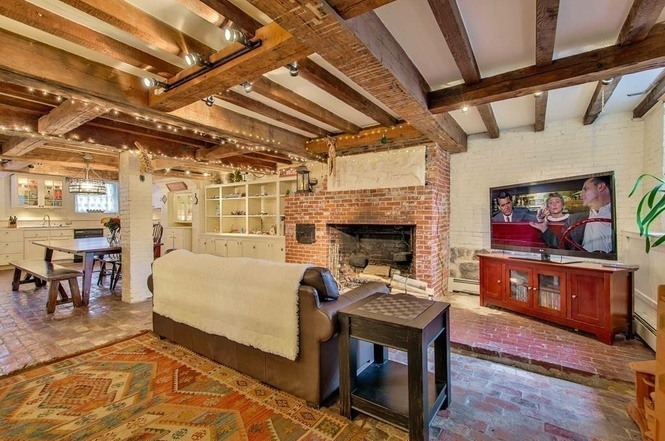 basement kitchen and family room with brick floors and fireplace