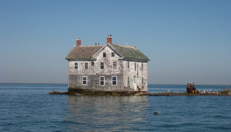 house swallowed by rising sea levels - flood insurance climate change global warming real estate