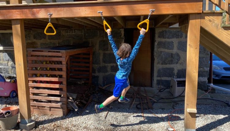 backyard monkey bars installed under deck