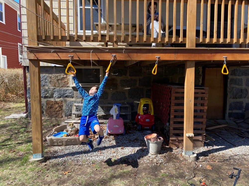 kid swinging on backyard diy monkey rings