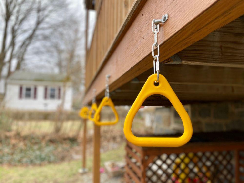 backyard monkey bars installed under deck