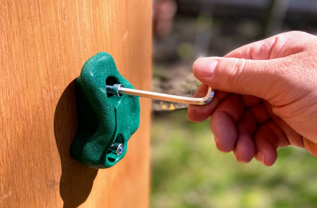securing handholds to backyard climbing wall