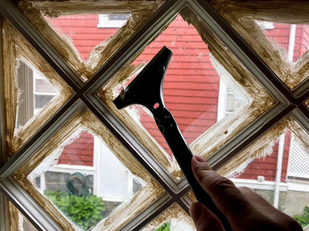 scraping excess paint off window panes